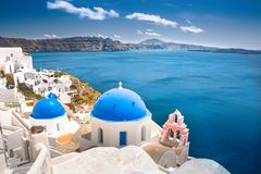 Oia town on Santorini island, Greece. Traditional and famous houses and churches with blue domes over the Caldera. Royalty Free Stock Image