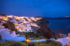 Oia town on Santorini island, Greece. Traditional and famous houses and churches with blue domes over the Caldera. Stock Photo