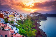 Oia town on Santorini island, Greece. Traditional and famous houses and churches with blue domes over the Caldera. Amazing sunsrise at Oia town on Santorini Royalty Free Stock Image