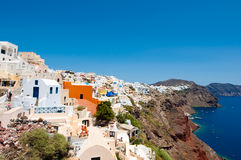 Oia traditional architecture with whitewashed buildings carved into the rock on the edge of the caldera cliff. Stock Images