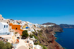 Oia traditional architecture with whitewashed buildings carved into the rock on the edge of the caldera on the island of Thera. Royalty Free Stock Image