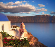 Oia village, Santorini island, Greece on a sunset. With local curch overlooking famous volcanic caldera. Panoramic toned image Royalty Free Stock Photography