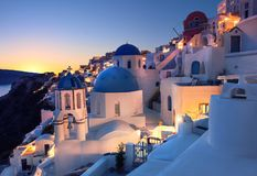 Oia village, Santorini island, Greece on a sunset. With local church overlooking famous volcanic caldera. Panoramic toned image Royalty Free Stock Photography