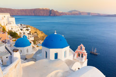 Oia village on Santorini island, Greece. World famous traditional whitewashed chuches and houses of Oia village on Santorini island, Greece. Sunset light Stock Photography