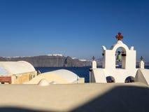 Oia - vista de la iglesia blanca y de la ciudad de Santorini en Fotografía de archivo