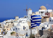 Oia Windmills And Greek Flags - Santorini Island. View of windmills in Oia in a summer day with Greek flags Royalty Free Stock Image