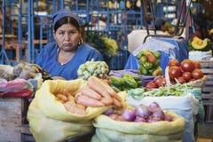 Oidentifierad bolivian kvinna som säljer frukt och grönsaker på den centrala marknaden i Sucre, Bolivia Royaltyfri Bild
