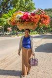 Oidentifierad burmese kvinna som bär den stora korgen av blommor på gator av Bagan, Myanmar Royaltyfri Fotografi