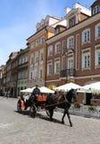 Oidentifierad familj som tycker om hästvagnsritt på den gamla staden Arkivbild