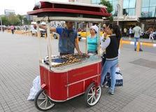 Oidentifierad grabb som säljer den grillade kastanjen på den Taksim fyrkanten Arkivfoton