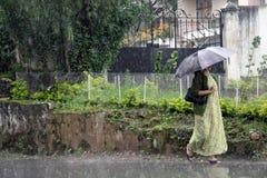 Oidentifierad kvinna i regn med ett paraply Arkivbild
