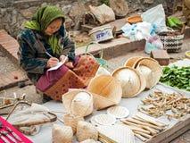 Oidentifierad kvinna som säljer traditionella asiatiska koniska hattar laos Arkivfoton