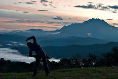Oidentifierad kvinna som sträcker på det utomhus- med Mount Kinabalu Royaltyfria Bilder