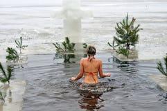 Oidentifierad kvinnasimning i kallt vatten under Epiphany Royaltyfri Fotografi