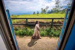 Oidentifierad lokal kvinna som framme går av drevdörrarna Royaltyfria Bilder