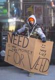 Oidentifierad man med tecknet som frågar för pengar att köpa ogräset på Broadway under vecka för Super Bowl XLVIII i Manhattan Arkivbild