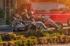 Oidentifierad man- och kvinnaridning till och med staden på en motorcykel på en solig dag royaltyfri bild