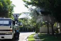 Oidentifierad man på vattenlastbilen som bevattnar det stora trädet royaltyfria bilder