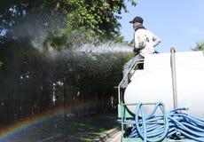 Oidentifierad man på vattenlastbilen som bevattnar det stora trädet royaltyfri foto