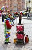 Oidentifierad man som täckas i plast- blommor för att göra show och tjäna pengar på slottfyrkanten Arkivbild