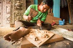 Oidentifierad nepalesisk man som arbetar i det hans wood seminariet, December 19, 2013 i Bhaktapur, Nepal Royaltyfri Fotografi