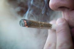 Oidentifierad person som röker den gemensamma drogcloseupen för marijuana Arkivfoto