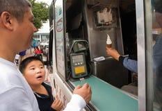 Oidentifierad pojke med väntande på glass för fröjdframsida i linje av folk Royaltyfri Fotografi