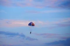 Oidentifierad skydiver, fallskärmshoppare på blå himmel Arkivfoto