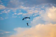 Oidentifierad skydiver, fallskärmshoppare på blå himmel Arkivbild