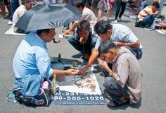 Oidentifierad thailändsk buddism kontrollerar på buddha amuletter Fotografering för Bildbyråer