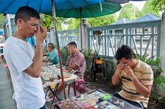 Oidentifierad thailändsk buddism kontrollerar på buddha amuletter Arkivfoto