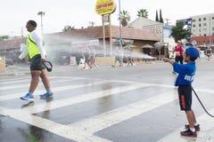 Oidentifierad volontärpojke som kastar vatten i en löpare Royaltyfria Bilder