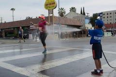 Oidentifierad volontärpojke som kastar vatten i en löpare Fotografering för Bildbyråer
