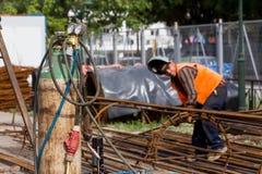 Oidentifierade arbetare som arbetar med konkret järn på en constructio Royaltyfri Foto