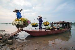 Oidentifierade bönder bär blommor till marknaden Arkivbilder