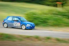 Oidentifierade chaufförer på blåa tappningPeugeot 106 en tävlings- bil Arkivfoto