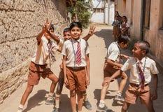 Oidentifierade indiska skolbarn som har gyckel med vänner i skolaborggården Arkivbild
