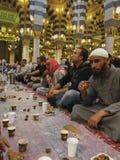 Oidentifierade muslimska män bryter snabbt på gryning inom den Nabawi moskén i Medina, Saudiarabien Royaltyfria Bilder