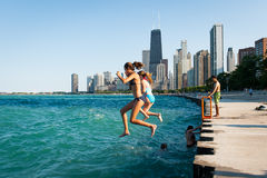 Oidentifierade tonåringar hoppar i Lake Michigan i Chicago, IL Royaltyfri Bild
