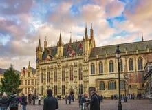 Oidentifierade turister nära gotiskt stadshus på småstadfyrkanten, Bruges, Belgien Arkivbilder