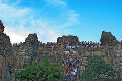 Oidentifierade turister som klättrar ett torn på Angkor Wat Royaltyfri Foto