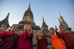 Oidentifierade unga buddismnoviser på Bagan Area visar upp tummen Arkivfoto