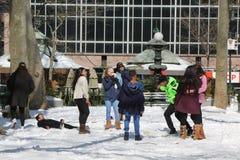 Oidentifierade ungar som tycker om insnöade Bryant Park, Midtown Manhattan Royaltyfri Bild