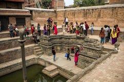 Oidentifierade vistors som besöker det berömda ormdammet på Royal Palace, Bhaktapur, Nepal Fotografering för Bildbyråer