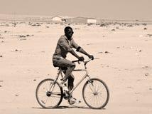 Oidentifierat barn som cyklar i den Mondesa slumkvarteret Royaltyfria Foton