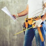 Oidentifierat byggmästareanseende i vita handskar med ett hjälpmedelbälte w Royaltyfri Bild