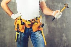 Oidentifierat byggmästareanseende i vita handskar med ett hjälpmedelbälte w Arkivbilder