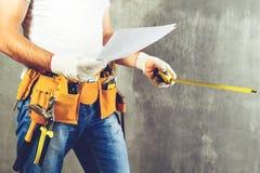 Oidentifierat byggmästareanseende i vita handskar med ett hjälpmedelbälte w Royaltyfria Bilder