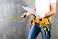 Oidentifierat byggmästareanseende i vita handskar med ett hjälpmedelbälte w Arkivfoto