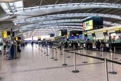 Oidentifierat folk på ett av den huvudsakliga slutliga vardagsrummet av den Heathrow flygplatsen Incheckningområde byggnadskungar arkivbilder